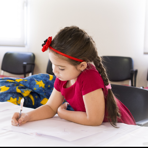 Young girl with dark hair writes with a pencil